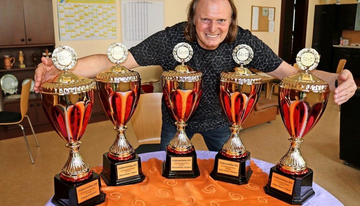 Grimmas Stadtmusikdirektor und JBO-Chef Reiner Rahmlow zeigt die Pokale, die vom Publikum an die beliebtesten Orchester vergeben werden. Foto: Frank Prenzel